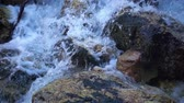 SLOW MOTION: flowing water over stones in mountines river