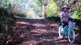 timeless : Girl rides bike through Autumn leaves in the fall Stock Footage