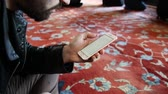 caligrafia : Muslim is reading Quran with mobile phone in a mosque Vídeos