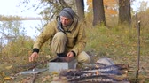 ohniště : the man hunter puts the shavings of the trees in the smokehouse. Bonfire on the river bank.