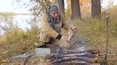 静かな : Fisherman smokes fish on fire, tourism
