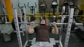 powerlifter strogman picks up the bar lying on an incline bench
