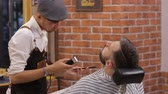 střih : bearded man having his beard cut by hairdresser at the barbershop
