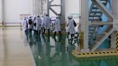 rehber : An excursion to the factory, people in White robes go through the factory workshop, which makes transformers Stok Video