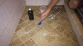 dezinfikovat : Person Scrubbing Shower Tile Floor.  One adult male cleaning grout in a shower tile floor. Low view of a man cleaning a shower tile floor with hydrogen peroxide and baking soda and a small scrub brush. Dostupné videozáznamy