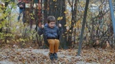 russo : Happy boy swinging on a swing in autumn Stock Footage