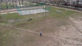 野球 : A man controls a drone in the playground. Automatic flight mode