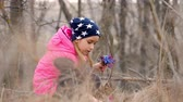 przebiśniegi : Beautiful young girl collects blue snowdrops in the forest
