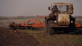 kurz : Tractor preparing land with seedbed cultivator as part of pre seeding activities of agricultural works at farmlands. Farmer in tractor preparing land with seedbed cultivator at sunset. Wideo