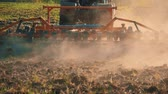 farming equipment : Tractor preparing land with seedbed cultivator as part of pre seeding activities of agricultural works at farmlands. Farmer in tractor preparing land with seedbed cultivator at sunset. Stock Footage
