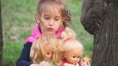 tremulação : Young girl playing with dolls on outdoors.