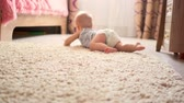 patro : Little baby boy of seven months, crawling on the floor at children room. Kid crawling on the carpet, back view.