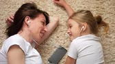 pajamas : Funny footage of young woman with little daughter lying on the floor looking at each other and listening to music on the phone, they use one earphone.