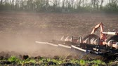 arando : Agricultural tractor sowing and cultivating field. Tractor with a plow trailer plowing the field after sunset.