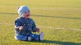 football field : Cute baby boy sitting at football field. Active childhood concept.