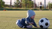 game field : Smiling baby boy with a soccer ball at football field. Portrait of a little child sitting at stadium with a ball. Future football star. Football training concept.