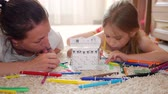 lakások : Young mother and her beautiful daughter, paint a paper house, lying on the floor at home, lifestyle, creativity, education. Stock mozgókép