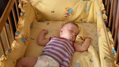 cot : Close up of a little baby boy sleeping, baby lying in baby cot.