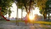 carvalho : Smiling little girl swaying on swing at golden summer sunset. Fun in park, in woods, in nature. A warm summer day.