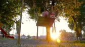 yardım : Smiling little girl swaying on swing at golden summer sunset. Fun in park, in woods, in nature. A warm summer day.