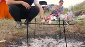 salsicha : A young and happy family who rests on a meadow with a tent frying meat sausages on skewers on fire, mom holding her little child, next to sit a daughter and husband who cooks dinner in the open air.