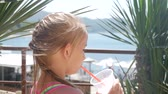 coquetel : A small and funny girl drinks fruit juice from a plastic cup with a straw against the backdrop of palm trees and the sea.