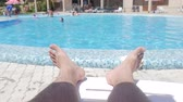 piscina : Enjoying summer vacation by the swimming pool, close up of male feet and poolside water on sunny summer day.