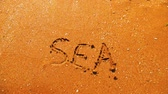 summer concept : The sea wave erases the inscriptions written on the sand. Top view. word sea.