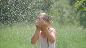famílias : Portrait of beautiful girl splashing water at garden. The girl gets wet completely its very hot and happy day . concept nature and happy kids water in slow motion, pure water concept. Stock Footage