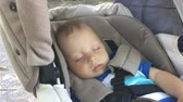 sen : Sweet little baby boy sleeping in stroller.