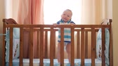 cot : Baby standing in bed at home. Portrait of baby boyl stand in cot. Baby eyes looking for mother.