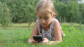 только один человек : Child using cellphone and lying in the green grass.