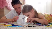 evler : Young mother and her beautiful daughter, paint a paper house, lying on the floor at home, lifestyle, creativity, education. Stok Video