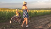 bisiklete binme : Family on bicycles in nature. Mom and daughter on bicycles on a field of sunflowers. Mother and daughter in hats are walking through sunflowers field. The concept of the family.