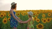 dia das mães : Mother and daughter at the sunflower field. Mother and daughter in hats are walking through sunflowers field. The concept of the family.