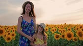 cheirando : Mother and daughter at the sunflower field. Mother and daughter in hats are walking through sunflowers field. The concept of the family.