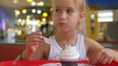 дегустация : Cute little girl is eating a cake in a cafe.