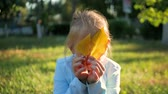 skrytý : Cute little girl hiding over yellow leaves. Autumn portrait smiling child hides her eyes yellow leaves. Dostupné videozáznamy