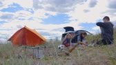 kids tent : Parents and kids having a picnic and they are going to stay overnight in a tent. Traveler woman and children relaxing, playing outdoors near camping tent. Family holidays, leisure activity in forest.