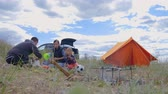 namiot : Parents and kids having a picnic and they are going to stay overnight in a tent. Traveler woman and children relaxing, playing outdoors near camping tent. Family holidays, leisure activity in forest.