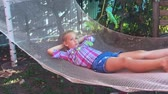 hamak : Cute child girl lying on hammock and relax at the garden.
