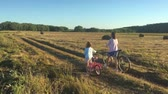 rowery : Mother with daughter on bicycles in a meadow. Family on bicycles in nature. The concept of the family.