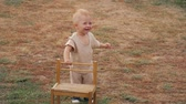 yardım : Baby boy walking with help of a chair outdoor.