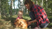 young mother : Mother with kid going on mushrooms picking in forest.