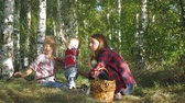 setas : Mother with kids going on mushrooms picking in forest.