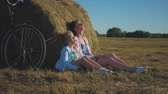 feno : Mother and daughter in a field with hay stack in a sunny day. Family mom with cheerful daughter they came by bicycle in the field. Lifestyle, family holiday, outdoor, concept.