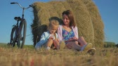 siano : Mother and daughter in a field with hay stack in a sunny day. Family mom with cheerful daughter they came by bicycle in the field. Lifestyle, family holiday, outdoor, concept.