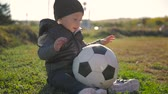 radostný : Smiling baby boy with a soccer ball at football field. Portrait of a little child sitting at stadium with a ball. Future football star. Football training concept.