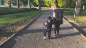 irmãs : Pretty girl holding hand and leading baby brother outdoors in autumn park. Stock Footage