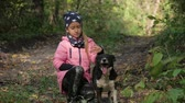 razem : Beautiful little girl together with a dog in the beautiful autumn park. Sunny weather. Close up. Outdoors. Wideo
